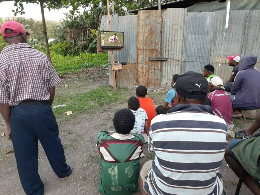 A crowd gathers around a small television in rural PNG to watch Justin Olam play earlier this season.