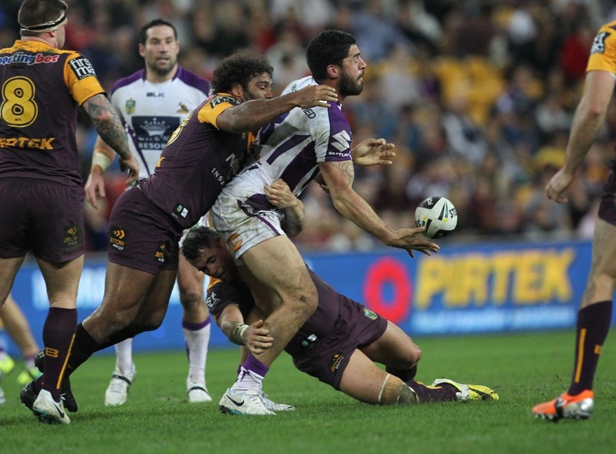 Photo by Colin Whelan copyright © nrlphotos.com :      Jesse Bromwich offloads as he is grabbed by Sam Thaiday and Corey Parker                         NRL Rugby League, Round 20 Brisbane Broncos v Melbourne Storm at Suncorp Stadium, Friday July 25th 2014.